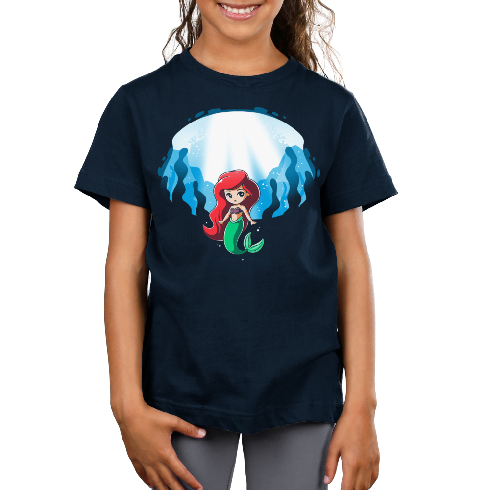Ariel and Ursula (Glow) Kid's t-shirt model officially licensed navy t-shirt featuring Ariel under water with Ursula who appears behind her when the shirt glows in the dark