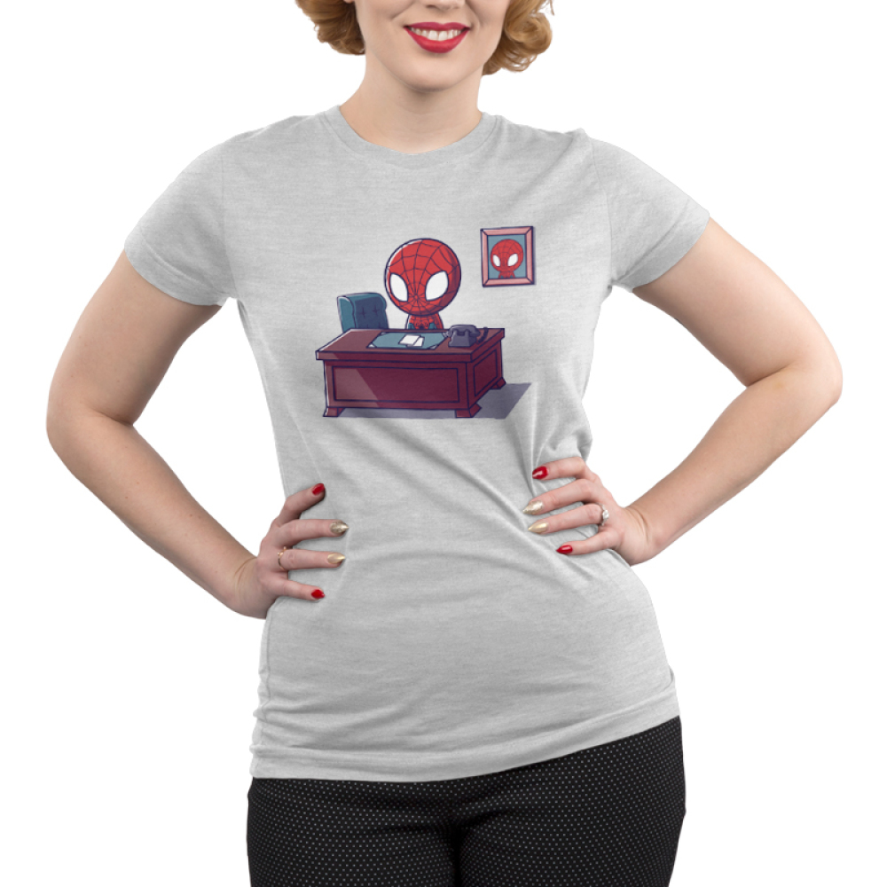 Desk Job Junior's t-shirt model officially licensed silver Marvel t-shirt featuring Spider-Man sitting at a brown desk with papers and a phone on it with a picture of him on the wall behind him