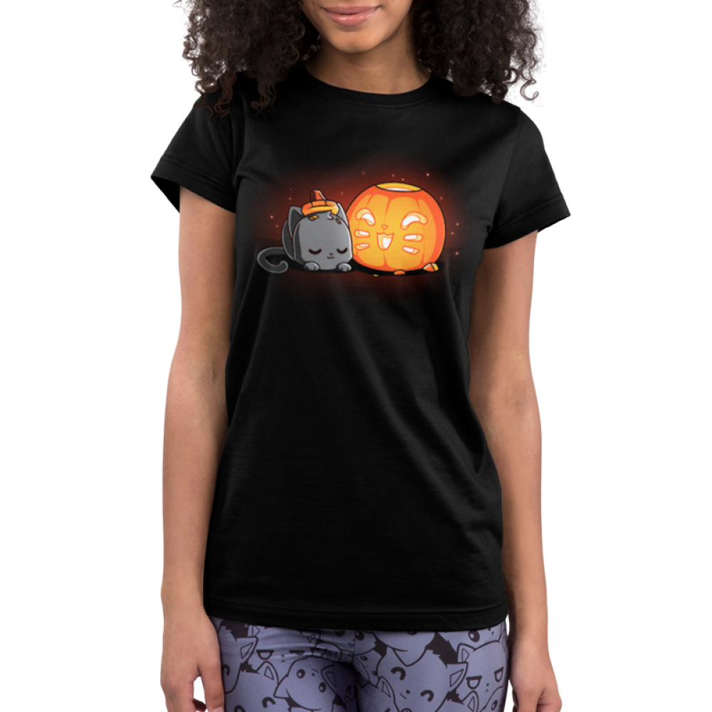 Pumpkin Carver Junior's t-shirt model TeeTurtle black t-shirt featuring a cute gray cat with its head down on its paws next to a pumpkin with a smiling cat face carved into it