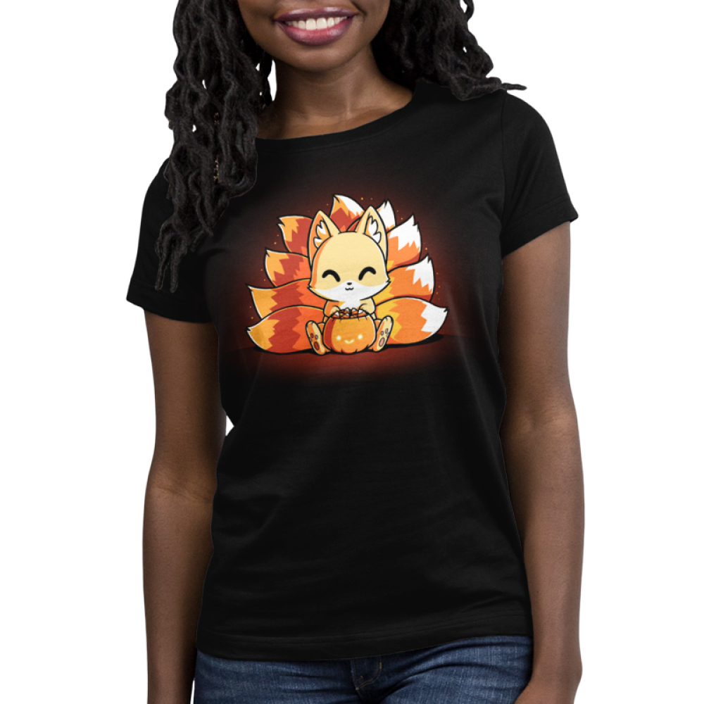 Candy Corn Kitsune Women's t-shirt model TeeTurtle black t-shirt featuring a kitsune sitting down with a basket that looks like a pumpkin full of candy in front of him with its tails in the three colors of candy corn