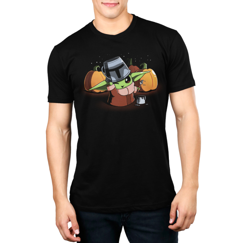 Mando Cosplay Men's t-shirt model officially licensed black t-shirt featuring The Child from The Mandalorian wearing a tin bucket thats been painting to look like the Mandalorian helmet with a buck of paint next to him and paint brush in his hand with three pumpkins behind him