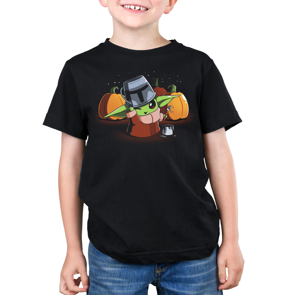 Mando Cosplay Kid's t-shirt model officially licensed black t-shirt featuring The Child from The Mandalorian wearing a tin bucket thats been painting to look like the Mandalorian helmet with a buck of paint next to him and paint brush in his hand with three pumpkins behind him