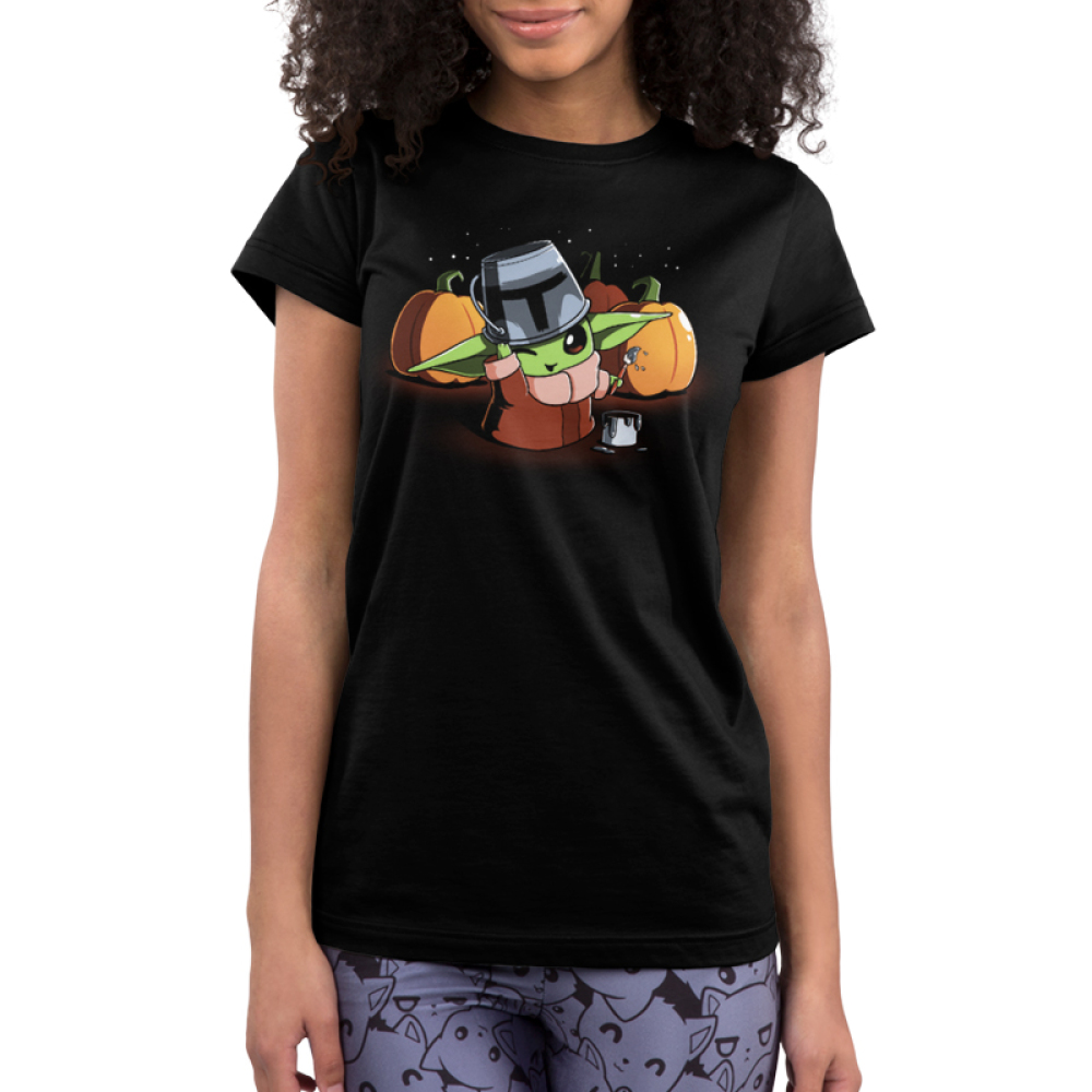 Mando Cosplay Junior's t-shirt model officially licensed black t-shirt featuring The Child from The Mandalorian wearing a tin bucket thats been painting to look like the Mandalorian helmet with a buck of paint next to him and paint brush in his hand with three pumpkins behind him