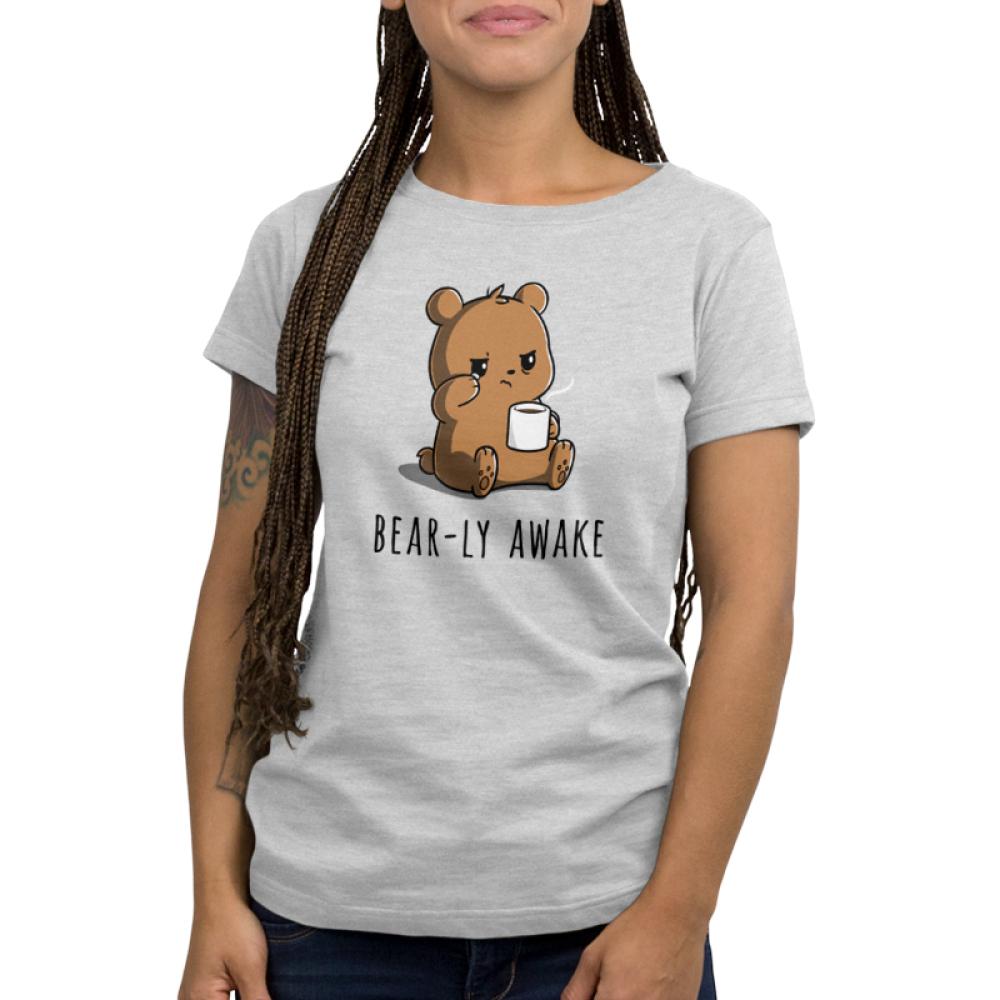 Bear-ly Awake Women's t-shirt model TeeTurtle silver t-shirt featuring a sleepy, grumpy brown bear rubbing his eye and holding a white mug of steaming coffee.