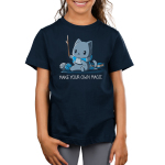 Make Your Own Magic Kid's t-shirt model TeeTurtle navy t-shirt featuring a gray cat in a blue and gray stripped shirt holding up a stick with balls of yarn and a book behind him