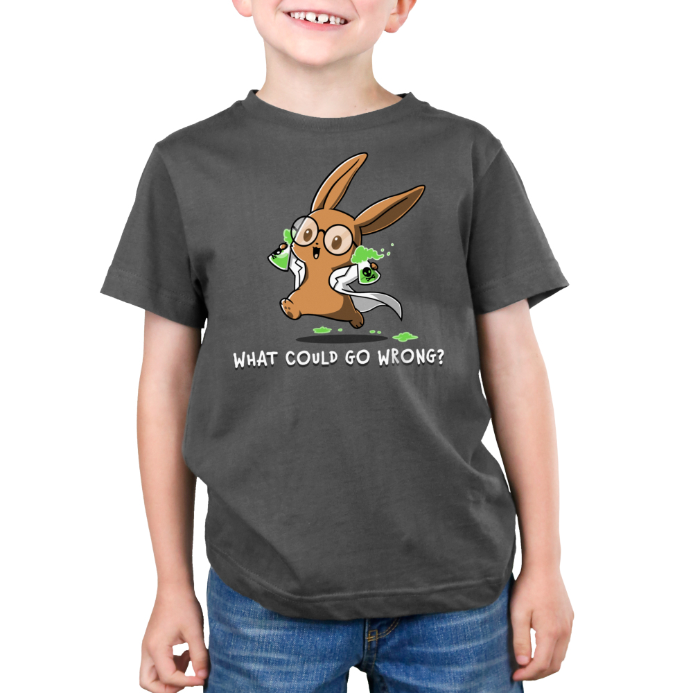 What Could Go Wrong Kid's t-shirt model TeeTurtle charcoal t-shirt featuring a light brown bunny with big circle glasses wearing a white lab coat holding two science flasks with skulls on them filled with green bubbling liquid