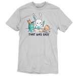 That Was Easy t-shirt TeeTurtle silver t-shirt featuring a white bunny covered in teal frosting holding a spatula standing in front of a teal cupcake and is surrounded by stacked mixing bowls, a rolling pin, a measuring cup, a frosting bag, an egg carton, and a bag of flour.