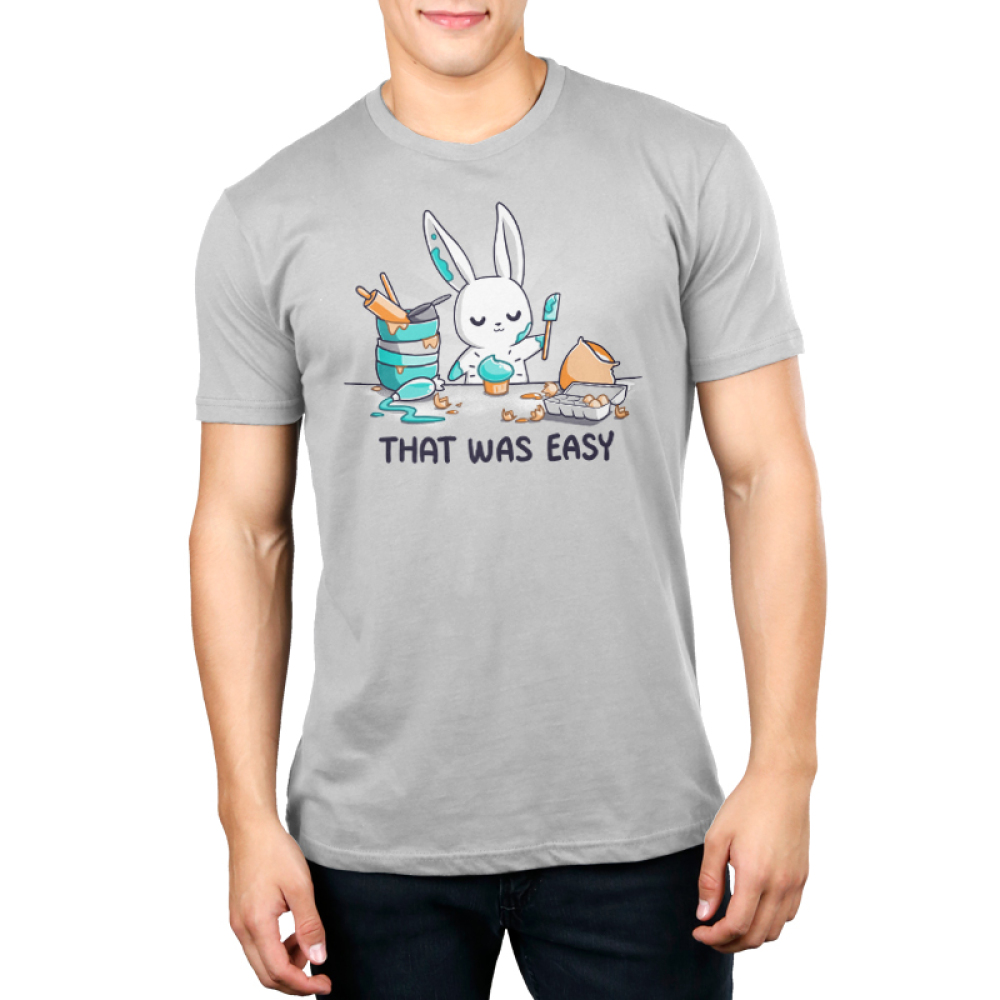 That Was Easy Men's t-shirt model TeeTurtle silver t-shirt featuring a white bunny covered in teal frosting holding a spatula standing in front of a teal cupcake and is surrounded by stacked mixing bowls, a rolling pin, a measuring cup, a frosting bag, an egg carton, and a bag of flour.