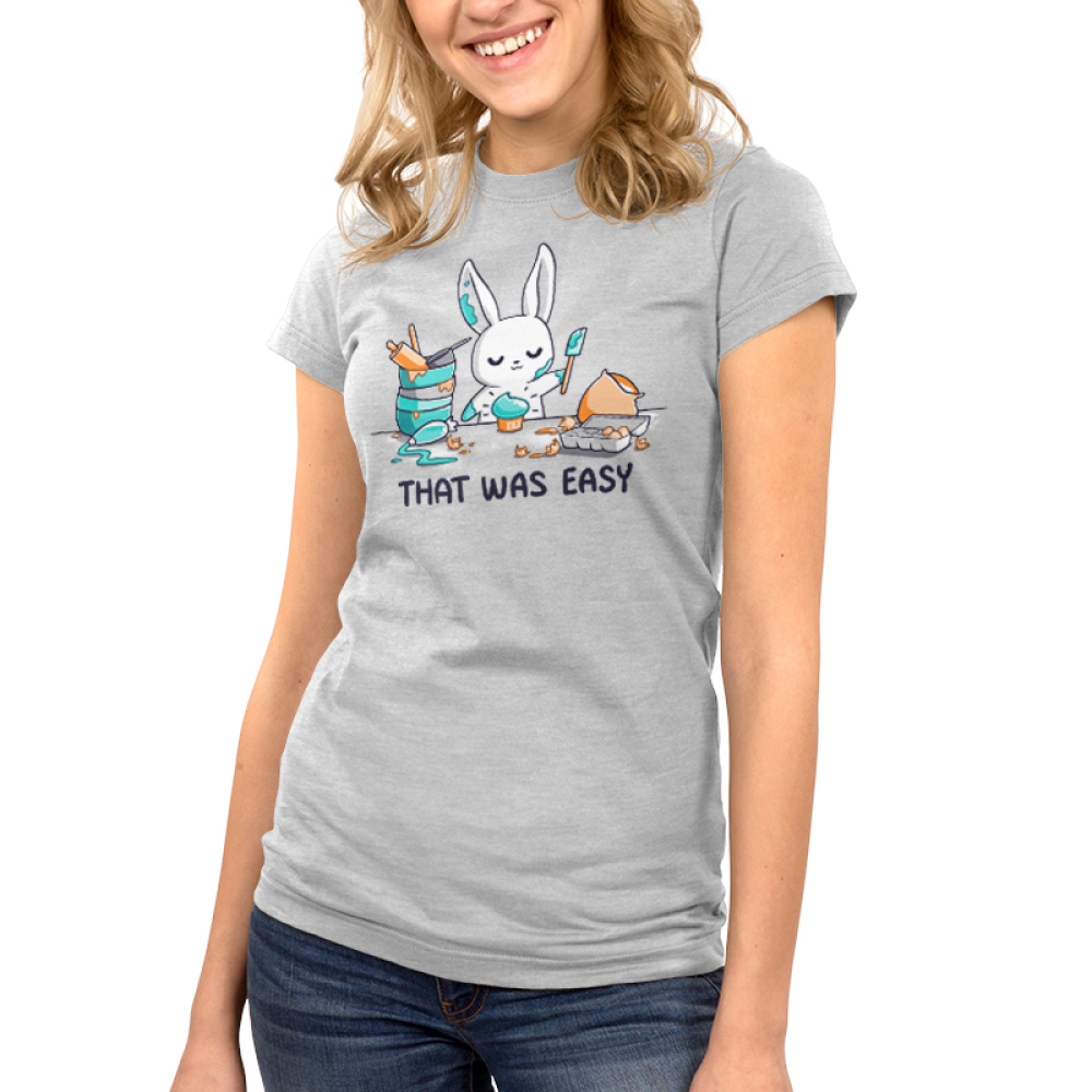 That Was Easy Junior's t-shirt model TeeTurtle silver t-shirt featuring a white bunny covered in teal frosting holding a spatula standing in front of a teal cupcake and is surrounded by stacked mixing bowls, a rolling pin, a measuring cup, a frosting bag, an egg carton, and a bag of flour.