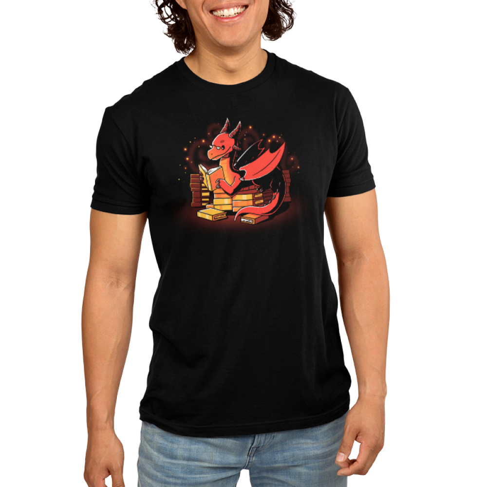 Book Hoarder Men's t-shirt model TeeTurtle black t-shirt featuring a happy, sparkling, red dragon with half-moon glasses sitting on top of a pile of golden books while reading a book.