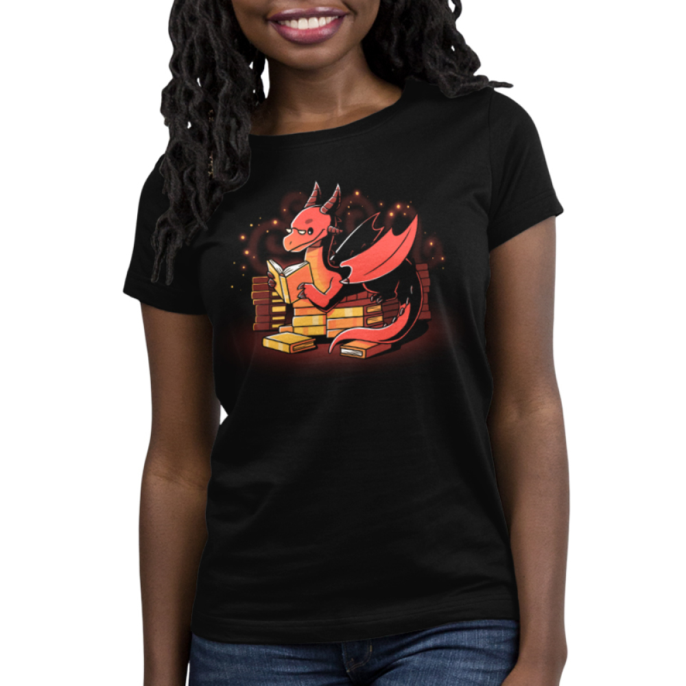 Book Hoarder Women's t-shirt model TeeTurtle black t-shirt featuring a happy, sparkling, red dragon with half-moon glasses sitting on top of a pile of golden books while reading a book.
