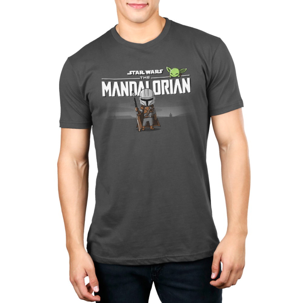 The Mandalorian Men's t-shirt model officially licensed charcoal Star Wars t-shirt featuring The Mandalorian logo up top with Mando standing underneath with his weapon in hand with The Child smirking above the logo