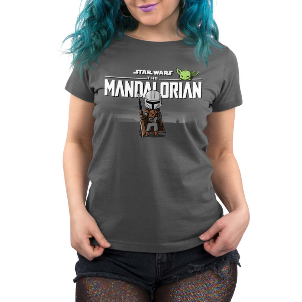 The Mandalorian Women's t-shirt model officially licensed charcoal Star Wars t-shirt featuring The Mandalorian logo up top with Mando standing underneath with his weapon in hand with The Child smirking above the logo