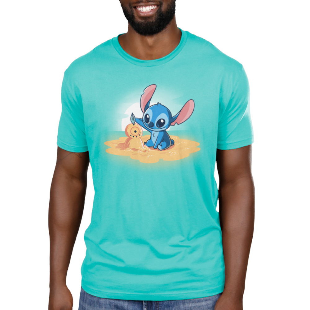Stitch's Snowman Men's t-shirt model officially licensed Caribbean blue Disney t-shirt featuring stitch on a little sand island surrounded by water making a snowman out of san with a sun set behind him