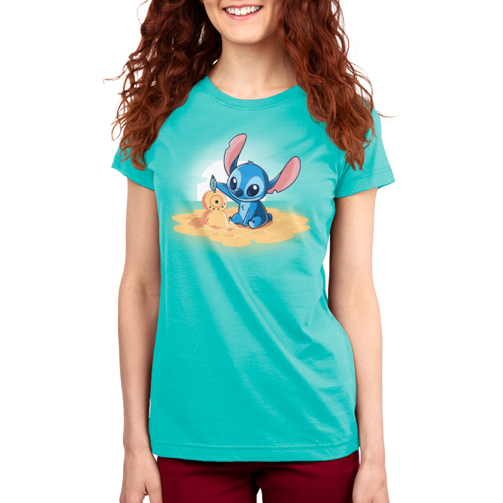 Stitch's Snowman Women's t-shirt model officially licensed Caribbean blue Disney t-shirt featuring stitch on a little sand island surrounded by water making a snowman out of san with a sun set behind him