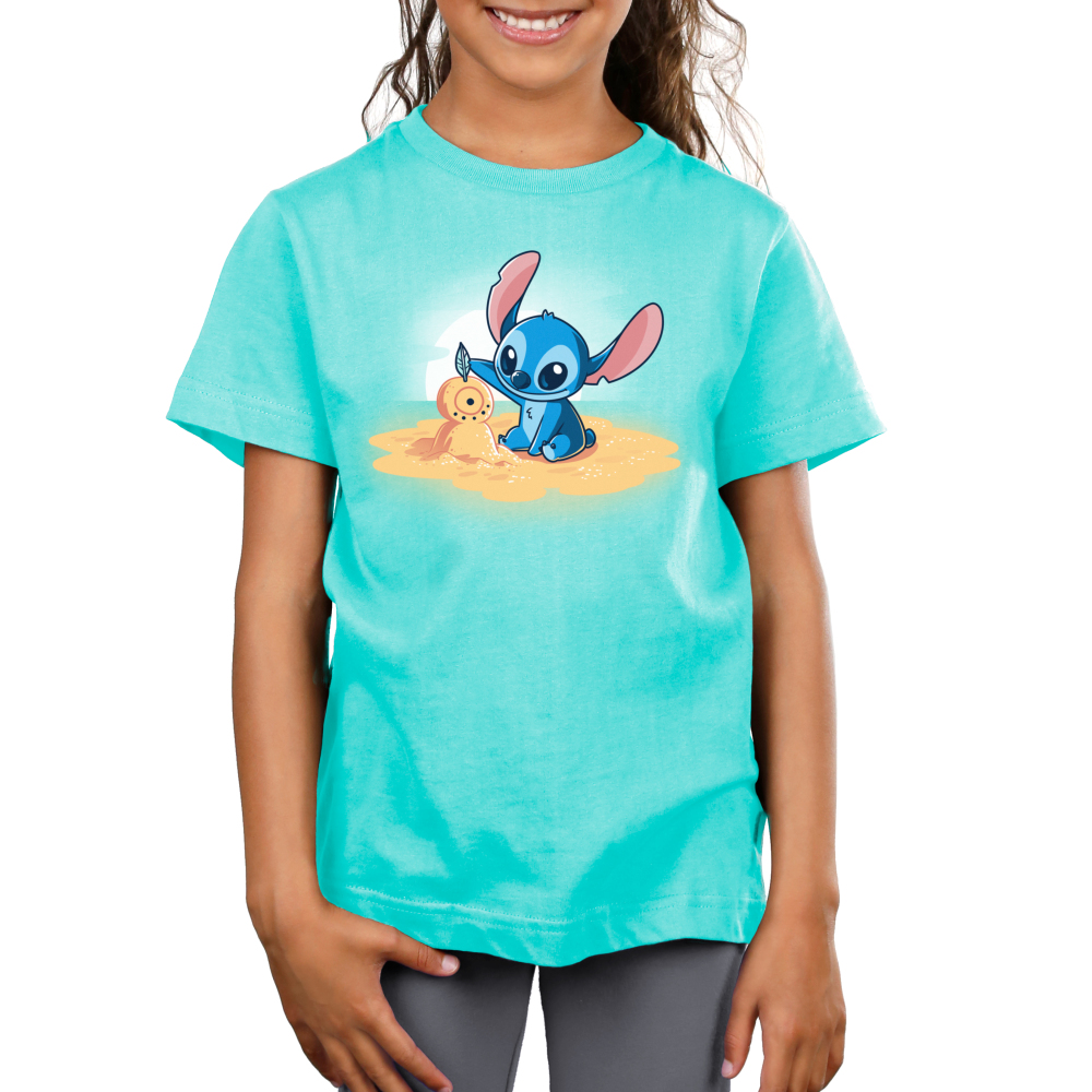 Stitch's Snowman Kid's t-shirt model officially licensed Caribbean blue Disney t-shirt featuring stitch on a little sand island surrounded by water making a snowman out of san with a sun set behind him