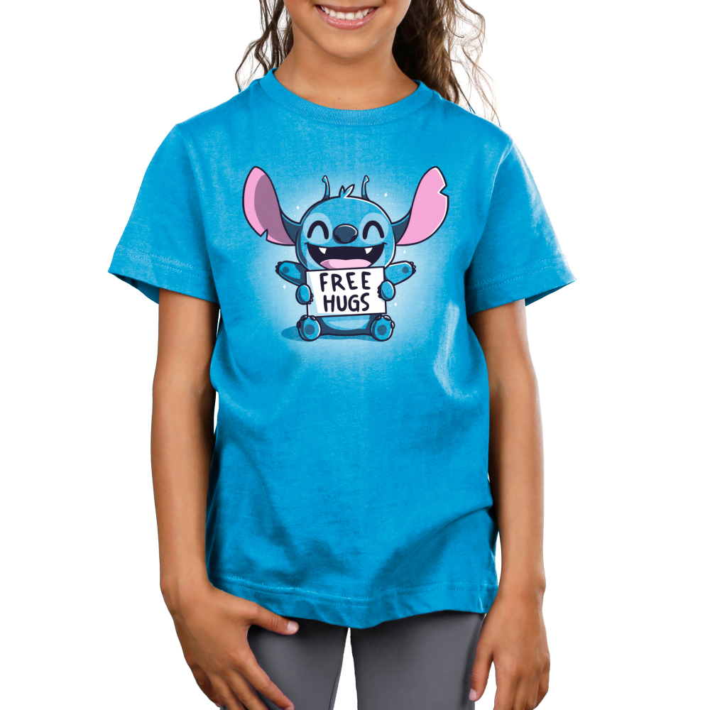 Free Hugs (Stitch) Kid's t-shirt model TeeTurtle cobalt blue t-shirt featuring a grinning, sparkling Stitch from Lilo and Stitch sitting down with his upper arms held out and his lower arms holding a sign saying,