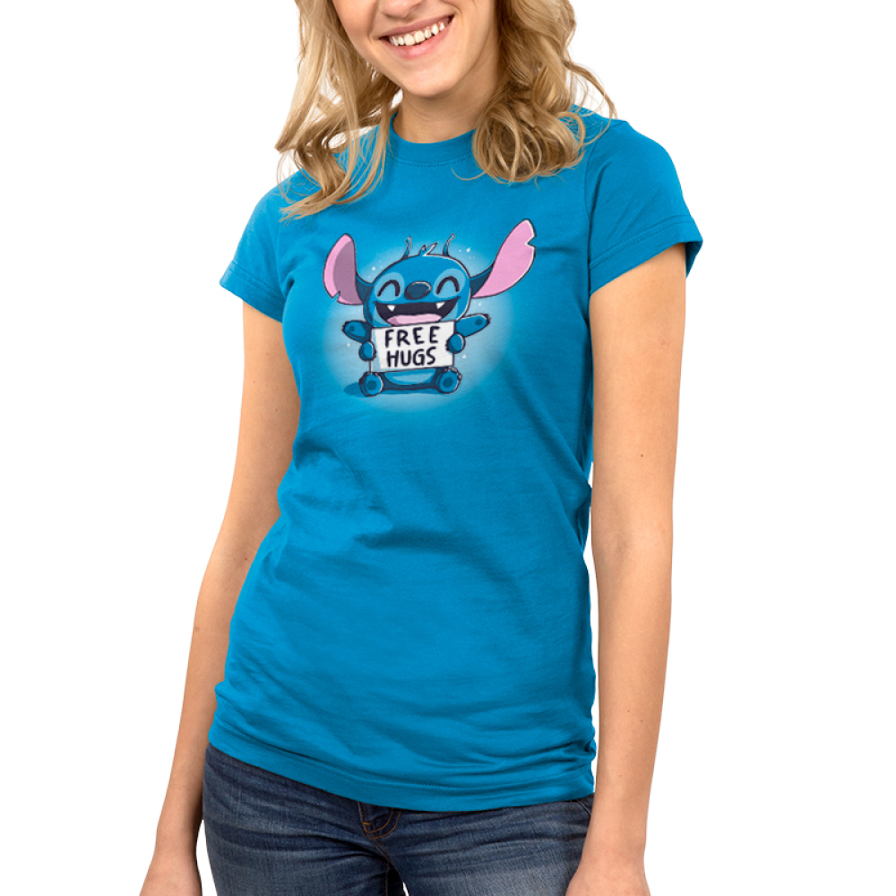 Free Hugs (Stitch) Junior's t-shirt model TeeTurtle cobalt blue t-shirt featuring a grinning, sparkling Stitch from Lilo and Stitch sitting down with his upper arms held out and his lower arms holding a sign saying,