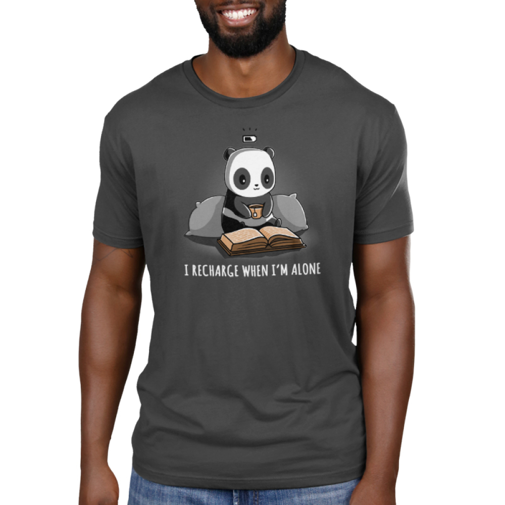 I Recharge When I'm Alone Men's t-shirt model TeeTurtle charcoal t-shirt featuring a panda with two big pillow behind him holding a cup of tea and reading a book laid out in front of him with a charging icon above his head