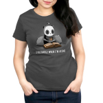 I Recharge When I'm Alone Women's t-shirt model TeeTurtle charcoal t-shirt featuring a panda with two big pillow behind him holding a cup of tea and reading a book laid out in front of him with a charging icon above his head