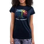 Look, a Rainbow! Junior's t-shirt model TeeTurtle navy t-shirt featuring a happy green brontosaurus on a hilltop looking at a rainbow-colored meteor shower with silhouetted palm trees in the distance.