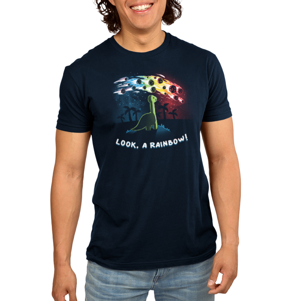 Look, a Rainbow! Men's t-shirt model TeeTurtle navy t-shirt featuring a happy green brontosaurus on a hilltop looking at a rainbow-colored meteor shower with silhouetted palm trees in the distance.