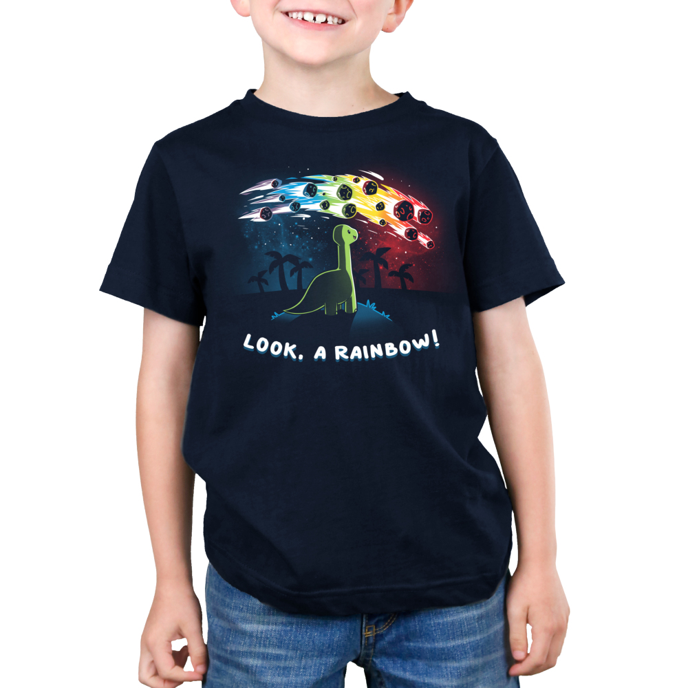 Look, a Rainbow! Kid's t-shirt model TeeTurtle navy t-shirt featuring a happy green brontosaurus on a hilltop looking at a rainbow-colored meteor shower with silhouetted palm trees in the distance.