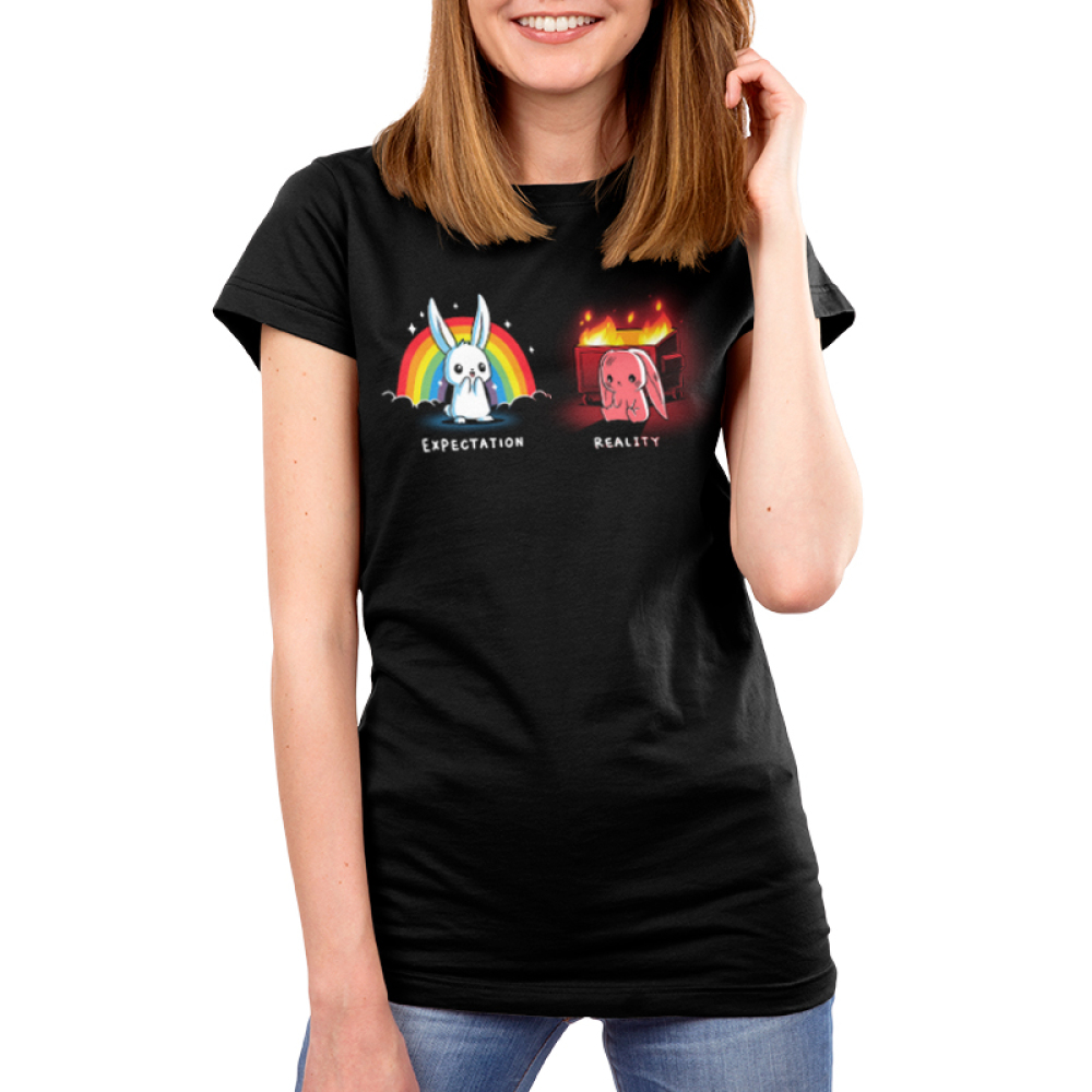 Expectation vs Reality (Bunny) Women's t-shirt model TeeTurtle black t-shirt featuring a white happy bunny on the left with a rainbow and sparkles behind him and a sad red colored bunny on the right with a burning trash bin behind him