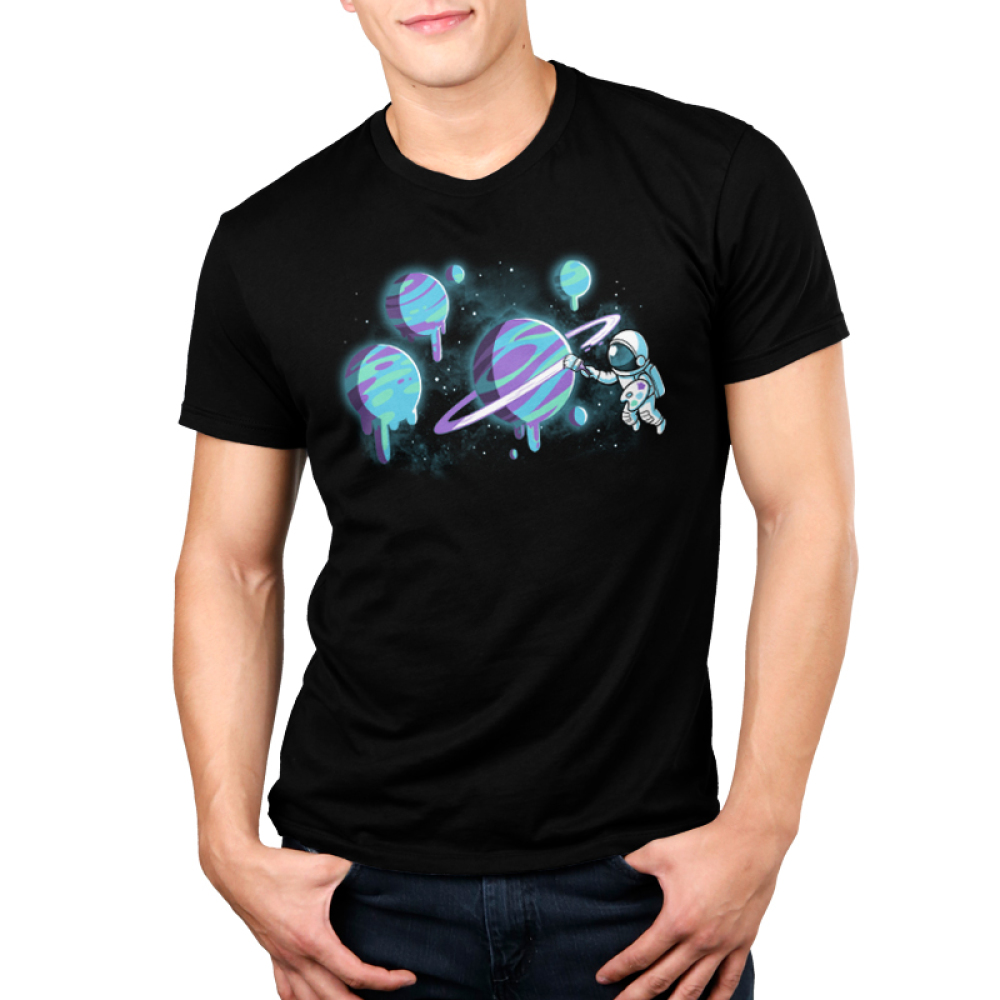 Astronaut Artist Men's t-shirt model TeeTurtle black t-shirt featuring an astronaut holding a painter's palette and painting the rings of a planet with several planets that they've painted in purple, blue, and green in the background.