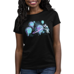 Astronaut Artist Women's t-shirt model TeeTurtle black t-shirt featuring an astronaut holding a painter's palette and painting the rings of a planet with several planets that they've painted in purple, blue, and green in the background.