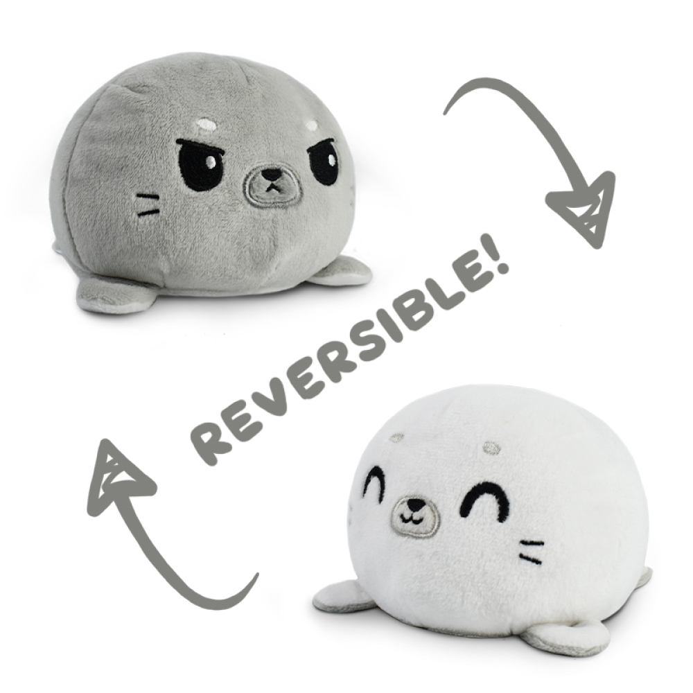 An angry gray reversible seal plushie flipping to a happy white reversible seal plushie.