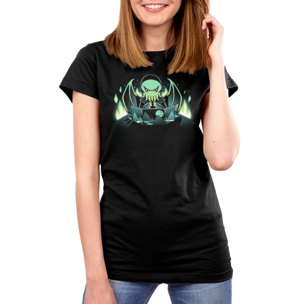 Dungeon Mster Women's t-shirt model TeeTurtle black t-shirt featuring a green winged Cthulu-humanoid dressed in a cloak menacingly rubbing his tentacles together behind a dungeon master's screen with a mountain landscape pattern and there's bright green flames in the background.