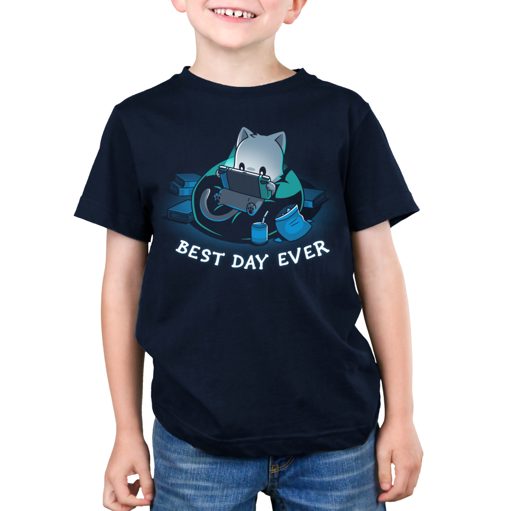 Best Day Ever Kid's t-shirt model TeeTurtle navy t-shirt featuring a cat in a bean bag chair holding a portal video game with snacks and books around him