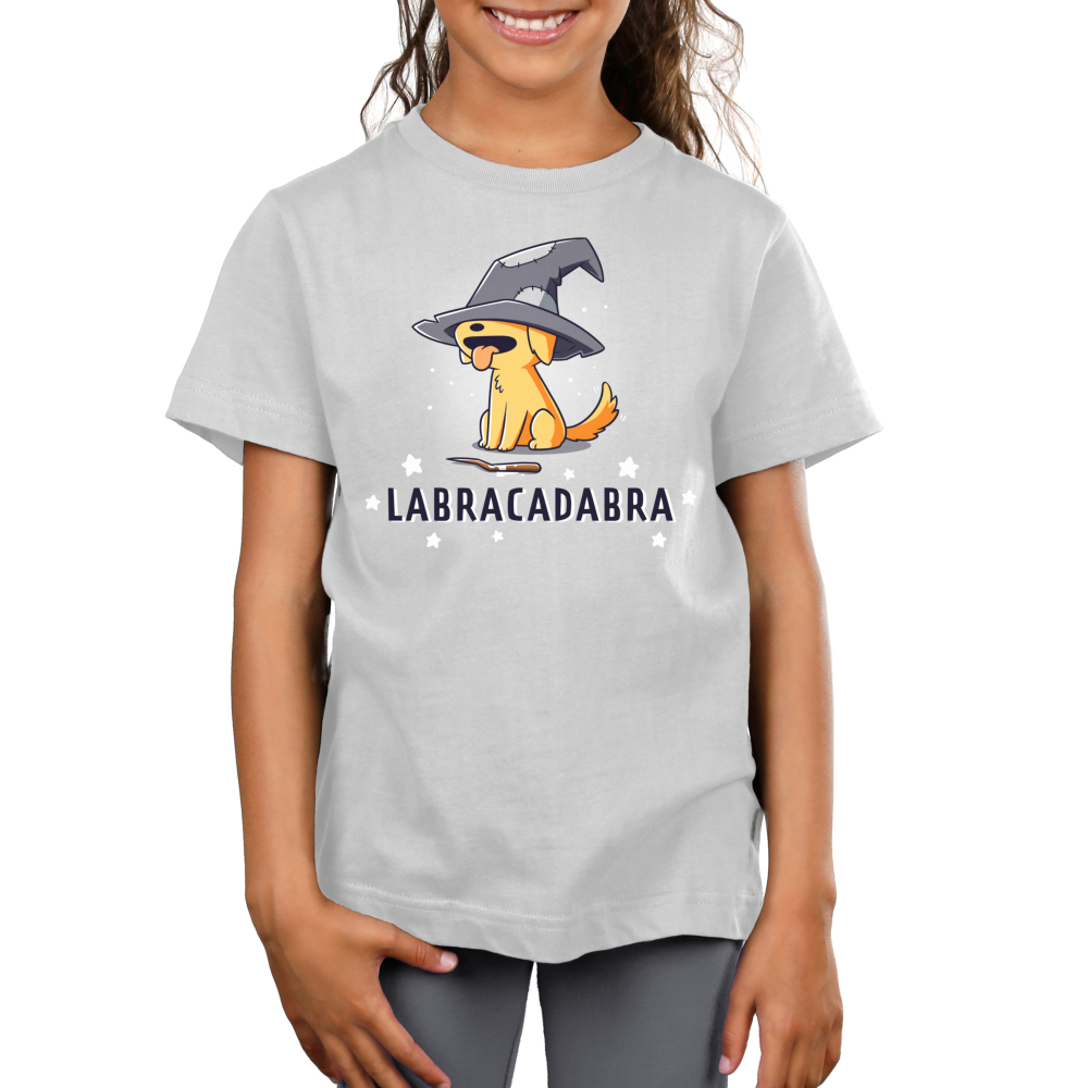 Labracadabra Kid's t-shirt model TeeTurtle silver t-shirt featuring a yellow lab smiling with its tongue out wearing a bit witch hat covering its eyes with a stick in front of him and stars all around him