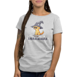 Labracadabra Women's t-shirt model TeeTurtle silver t-shirt featuring a yellow lab smiling with its tongue out wearing a bit witch hat covering its eyes with a stick in front of him and stars all around him