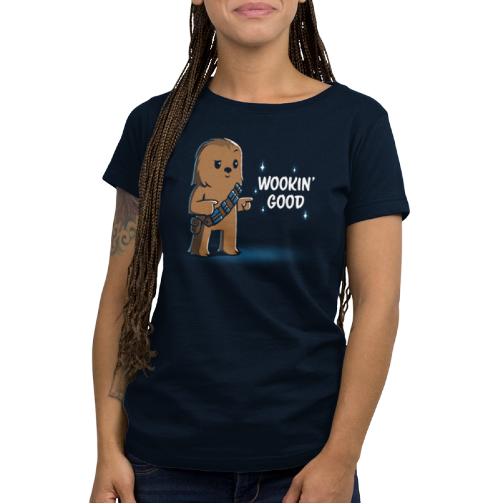 Wookin' Good Women's t-shirt model officially licensed navy Star Wars t-shirt featuring a smiling, suave Chewbacca from the Star Wars Sequel Trilogy doing finger guns with one eyebrow raised and one eyebrow lowered.