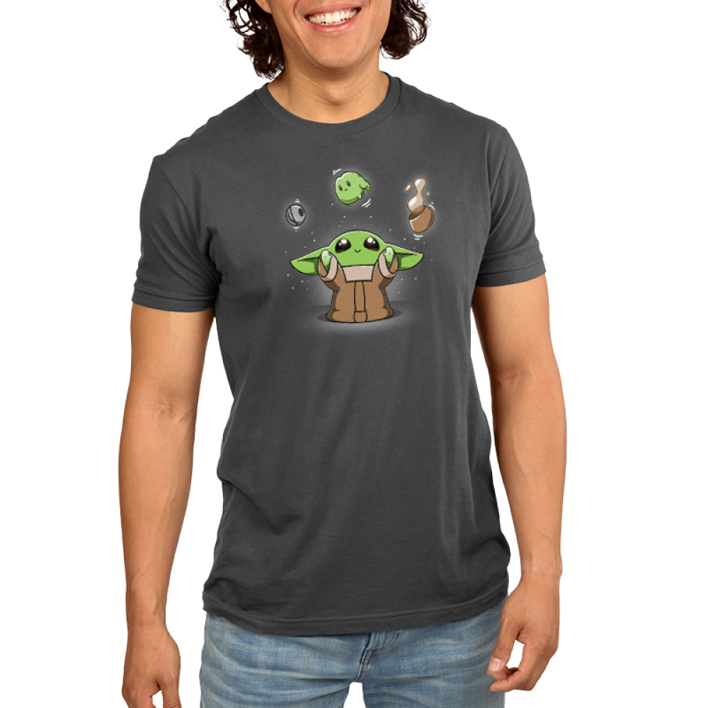 The Child Levitation Men's t-shirt model officially licensed charcoal Star Wars t-shirt featuring featuring The Child smiling and holding up its arms, making the metal ball from the Razor Crest, a frog, and a brown bowl of soup levitate above its head.
