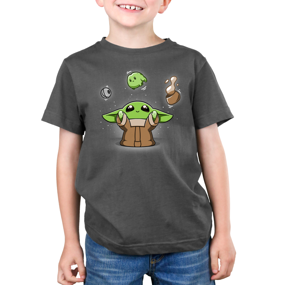 The Child Levitation Kid's t-shirt model officially licensed charcoal Star Wars t-shirt featuring The Child smiling and holding up its arms, making the metal ball from the Razor Crest, a frog, and a brown bowl of soup levitate above its head.