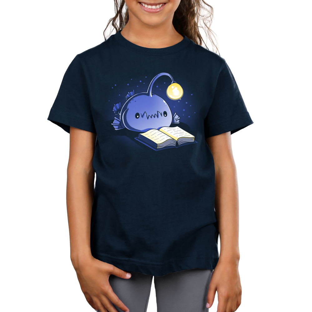 Reading Anglerfish Kid's t-shirt model TeeTurtle navy t-shirt featuring a blue anglerfish with its light glowing reading a book