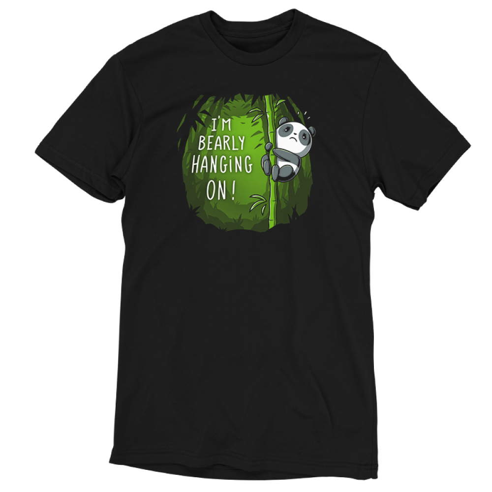I'm Bearly Hanging On TeeTurtle black t-shirt featuring an anxious panda hanging onto the middle portion of a bamboo shoot in a verdant green bamboo forest.