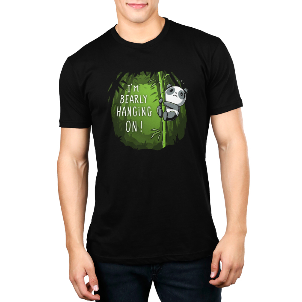 I'm Bearly Hanging On Men's t-shirt model TeeTurtle black t-shirt featuring an anxious panda hanging onto the middle portion of a bamboo shoot in a verdant green bamboo forest.