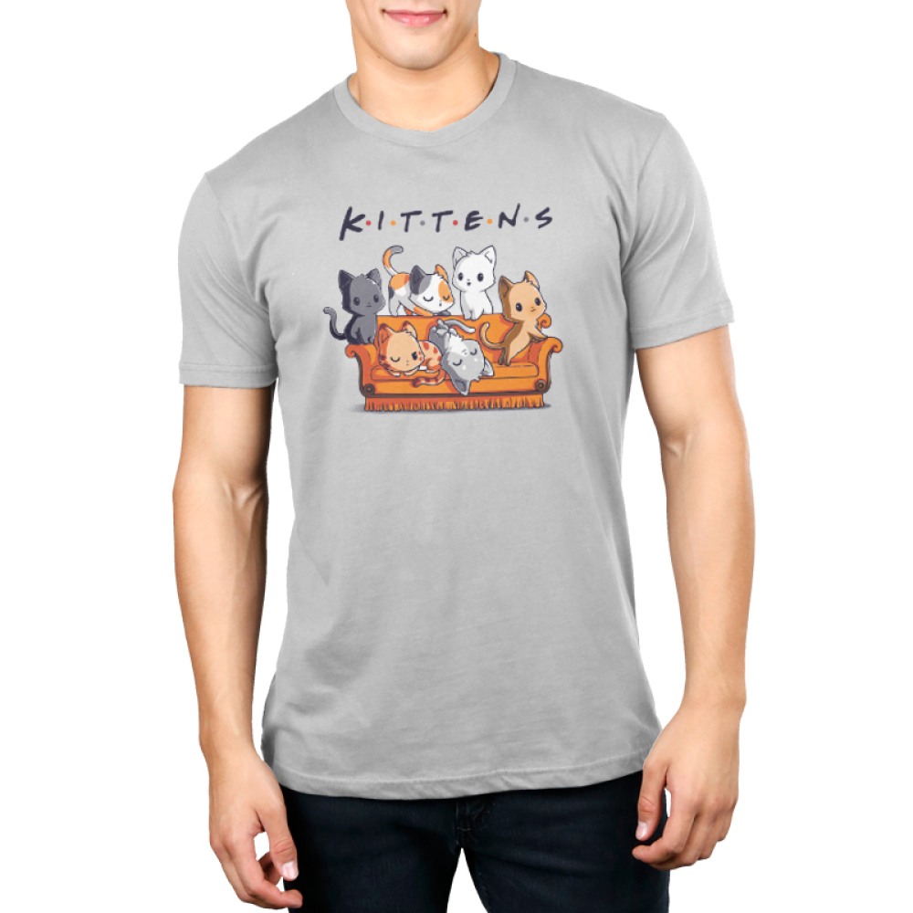 Kittens Men's t-shirt model TeeTurtle silver t-shirt featuring six cats on an orange couch, one charcoal cat, one calico cat, one white cat, one orange cat, one light gray and white cat, and one orange stripped cat all laying and crawling over the couch