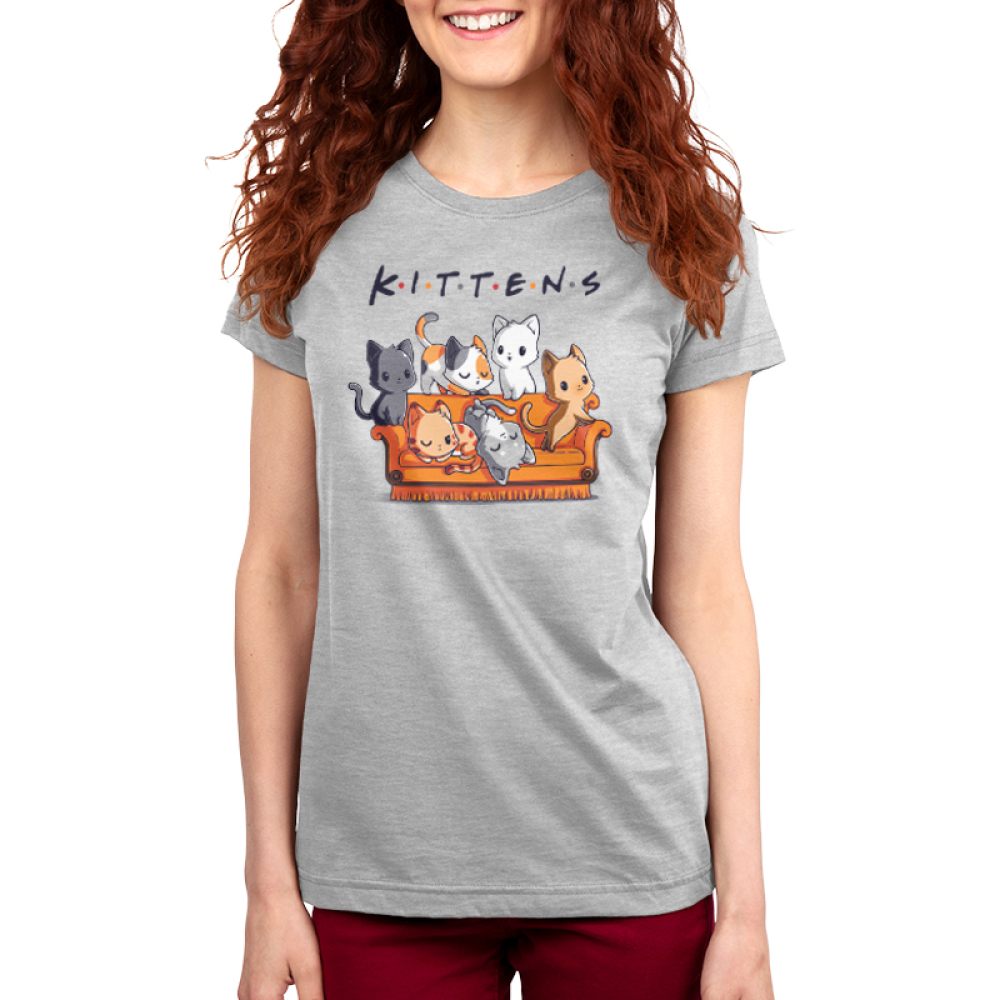 Kittens Women's t-shirt model TeeTurtle silver t-shirt featuring six cats on an orange couch, one charcoal cat, one calico cat, one white cat, one orange cat, one light gray and white cat, and one orange stripped cat all laying and crawling over the couch