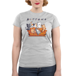 Kittens Junior's t-shirt model TeeTurtle silver t-shirt featuring six cats on an orange couch, one charcoal cat, one calico cat, one white cat, one orange cat, one light gray and white cat, and one orange stripped cat all laying and crawling over the couch