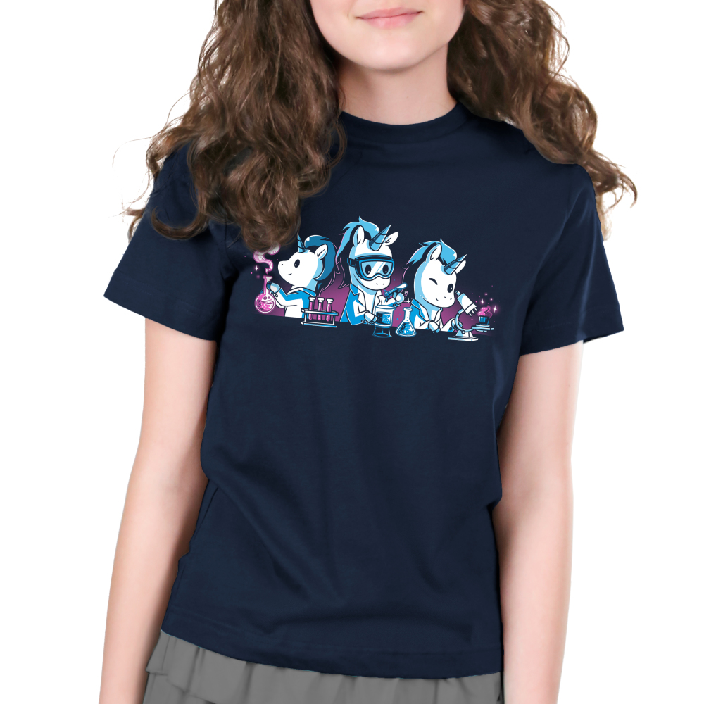 Unicorn Scientists Kid's t-shirt model TeeTurtle navy t-shirt featuring three white unicorns with blue manes in white lab coatssurrounded by lab equipment, with the lefthandunicorn holding a smoking beaker, the middle unicornpouring a test tubeinto a beaker, and the righthand unicorn inspecting a pink cupcake under a microscope.
