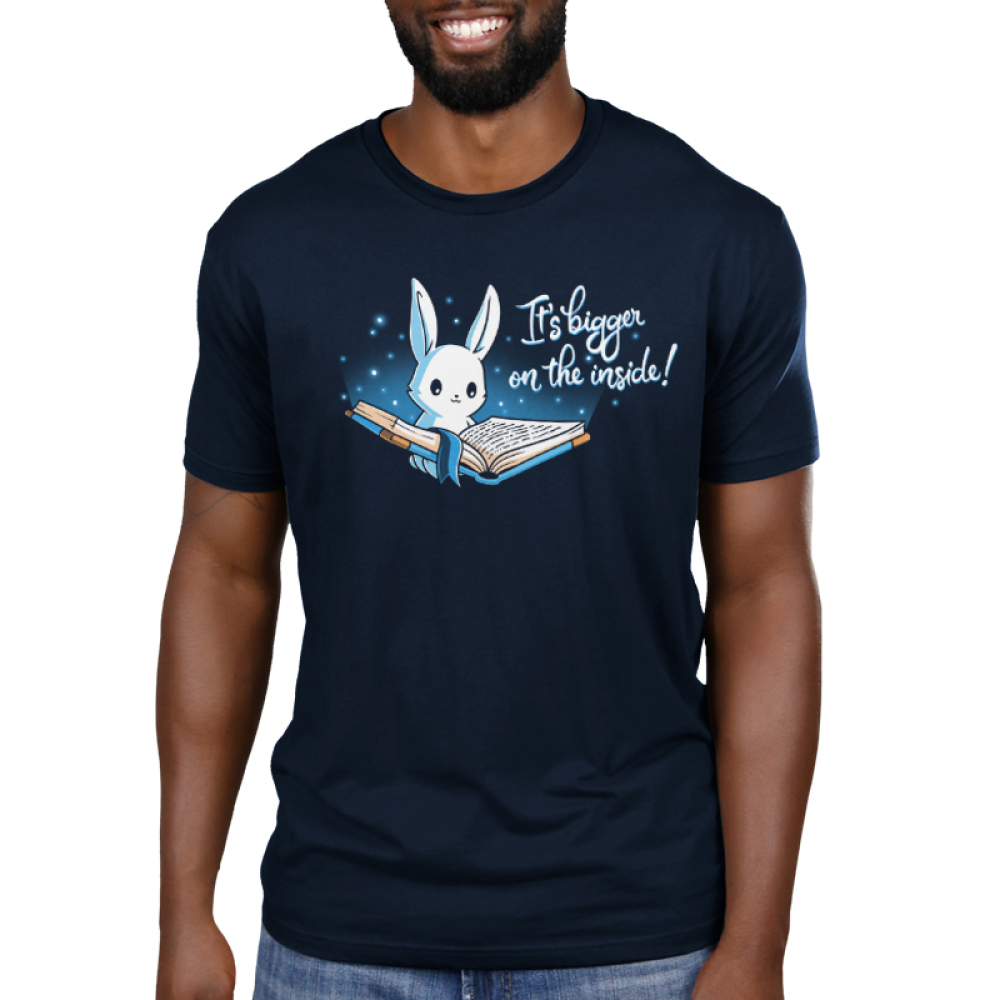 Books are Bigger on the Inside Men's t-shirt model TeeTurtle navy t-shirt featuring a bunny holding open a big blue book with a navy sky behind him and twinkling lights