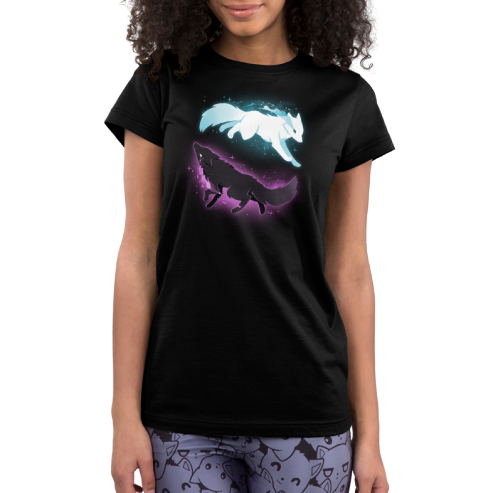 Celestial Spirits Junior's t-shirt model TeeTurtle black t-shirt featuring a white wolf with blue sparkles on the top running to the righthand side and a black wolf with purple sparkles on the bottom running to the lefthand side in such a way that they form a circle.