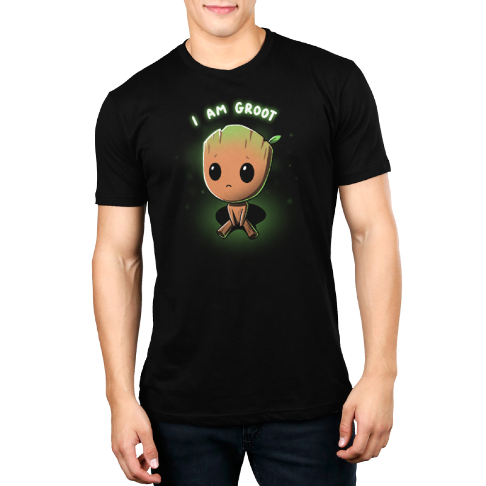 Pouting Groot Men's t-shirt model officially licensed black Marvel t-shirt featuring little Groot sitting down looking up looking sad with his eyes so big