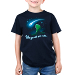 When You Wish Upon a Star Kid's t-shirt model TeeTurtle navy t-shirt featuring a little green t-rex on a grassy hilltop looking happily up at a shooting star against a starry sky.