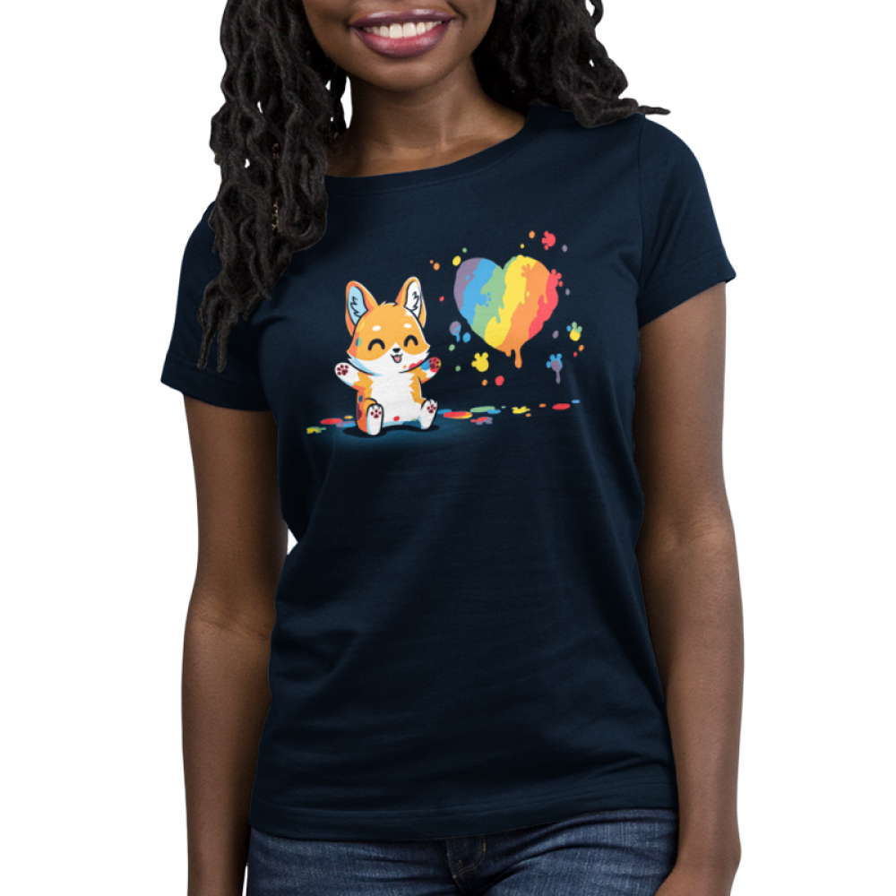 Paw Painting (Corgi) Women's t-shirt model TeeTurtle navy t-shirt featuring a corgi sitting up covered in multiple paint colors beside a rainbow heart with colorful pawprints and splatters all around.
